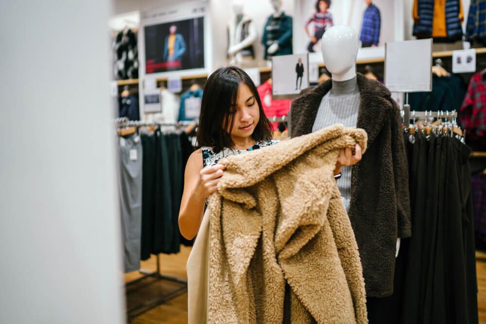 お店でコートを選ぶ女性