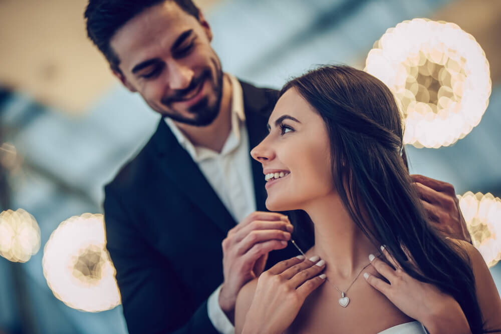 彼女にネックレスを贈る男性