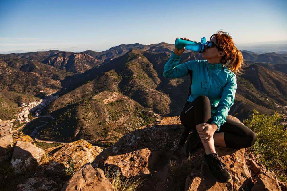 登山中に水を飲む女性