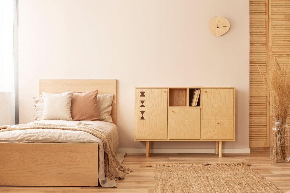 木材のチェストとベッドを置いた部屋