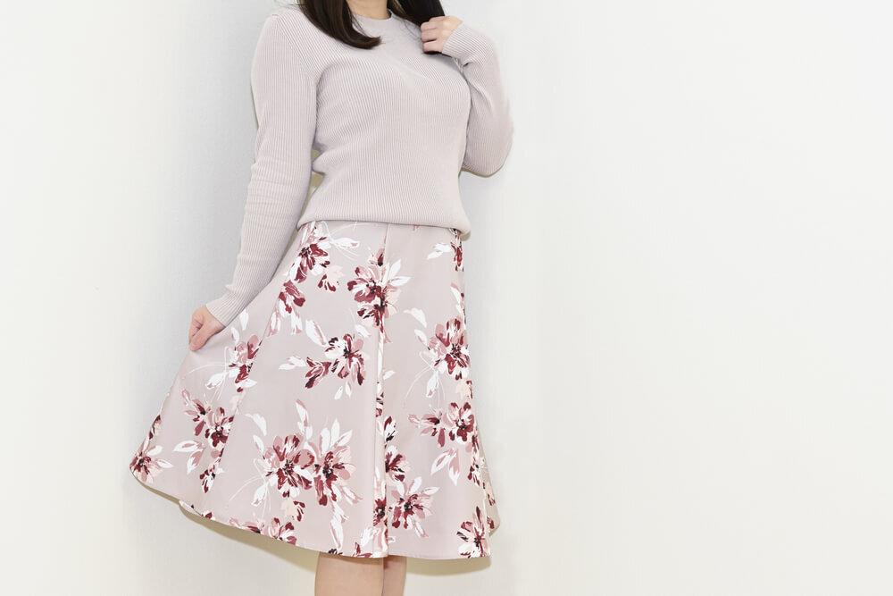 ニットと花柄スカートを着た女性