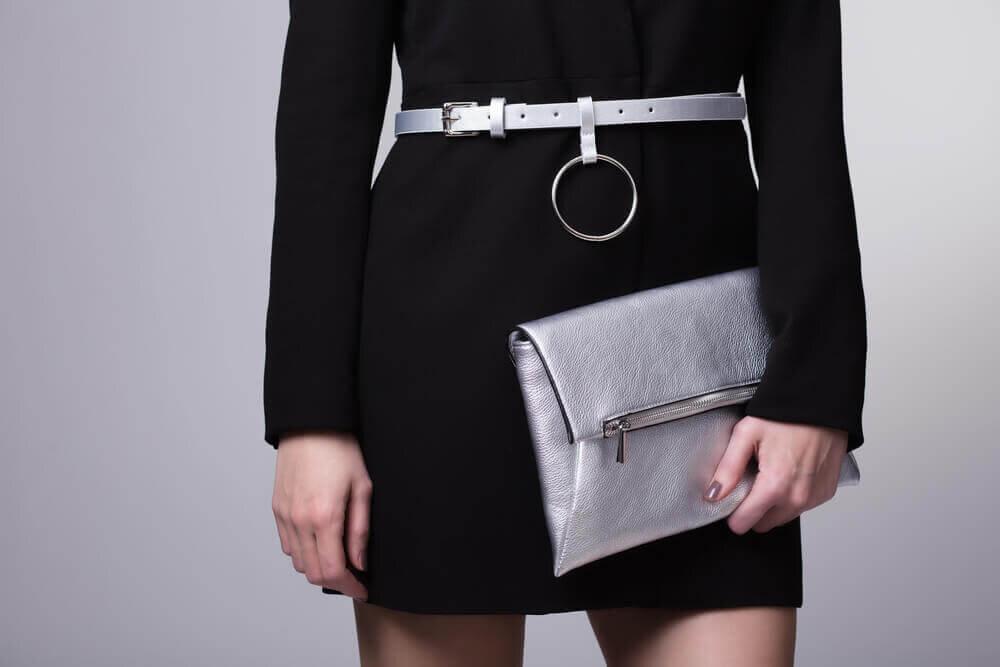 メタリックなクラッチバッグを持つ女性