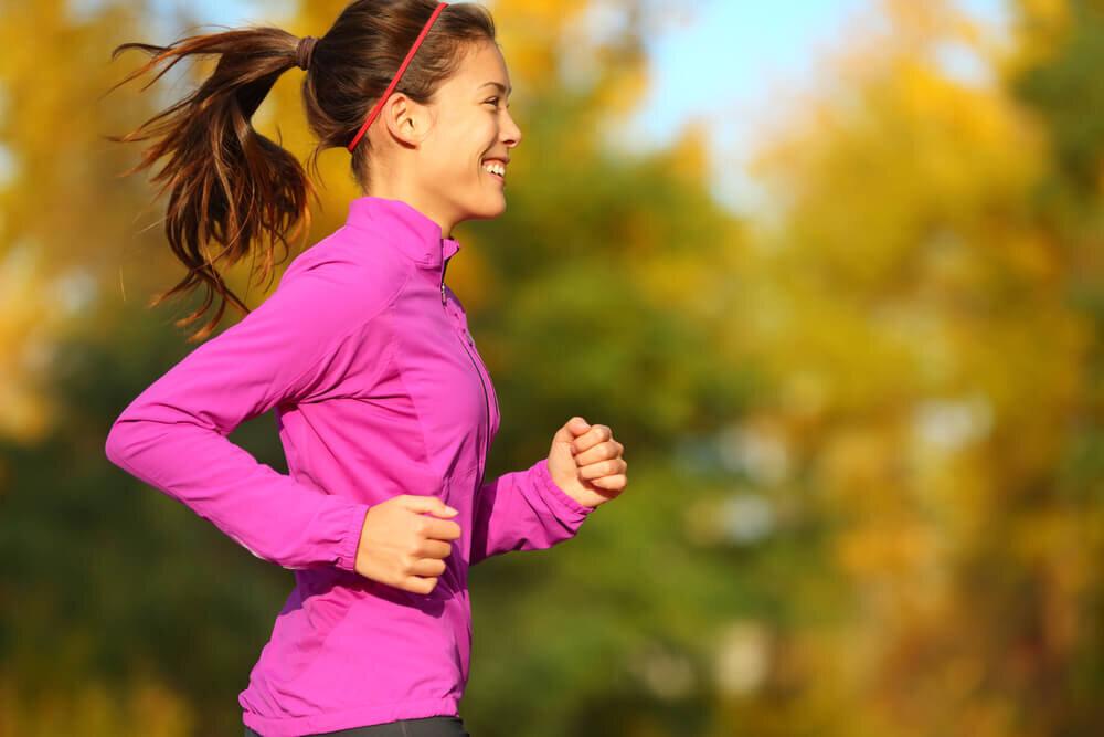ピンクのパーカーを着て走る女性