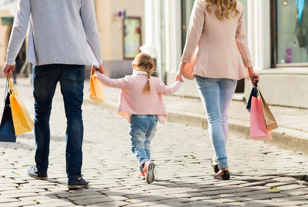 ショッピングバッグを持って歩く家族