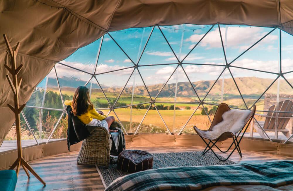 グランピング用のテントの中でくつろぐ女性
