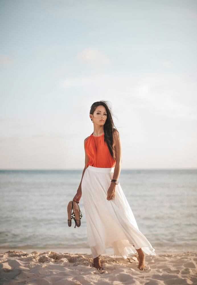 オレンジのトップスと白いスカートを着た女性