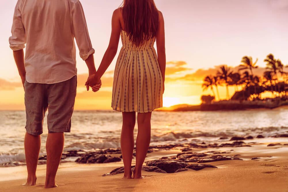 浜辺で夕日を見るカップル