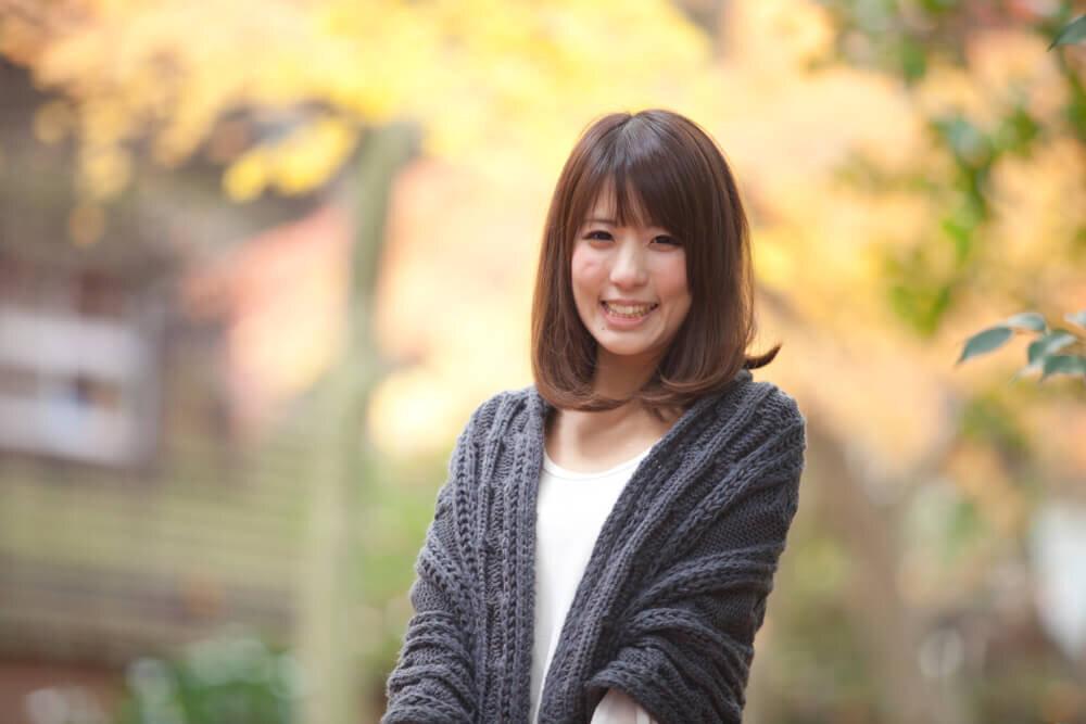 紅葉の中で笑いかける若い女性