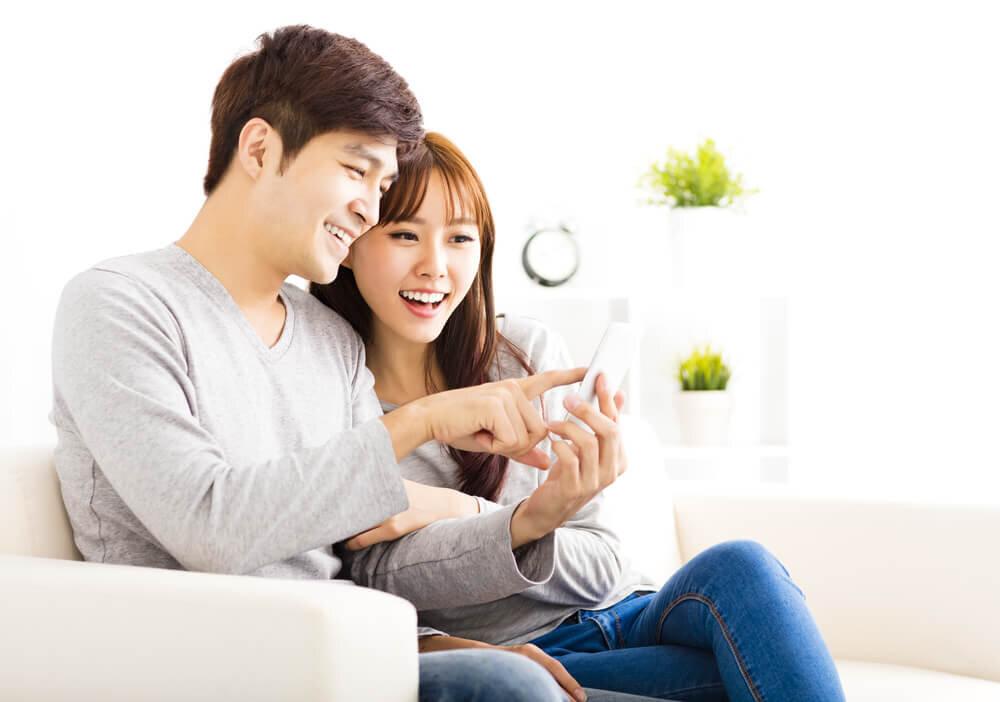 ソファに座ってスマートフォンを見ている若いカップル