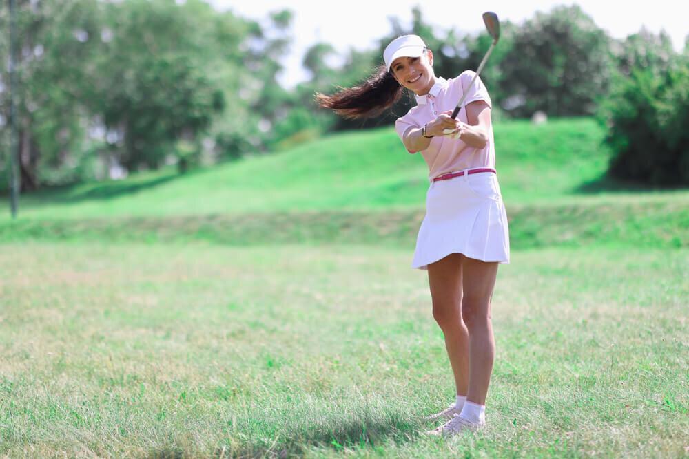 ピンクと白のゴルフウェアを着る女性
