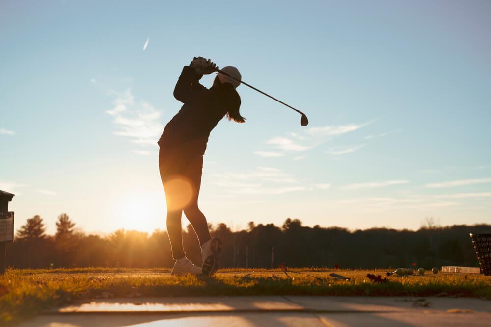 冬のゴルフ場でプレーする女性