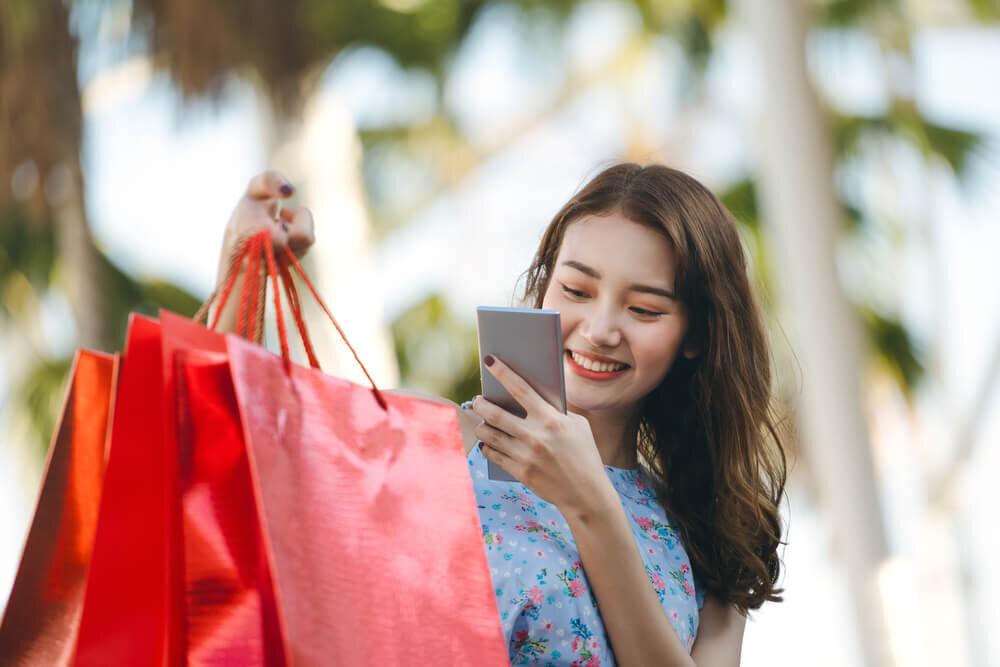 携帯見ながら紙袋を持つ女性