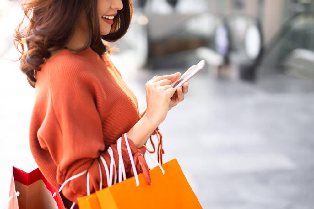 ショッピングをしながらスマホを見る女性