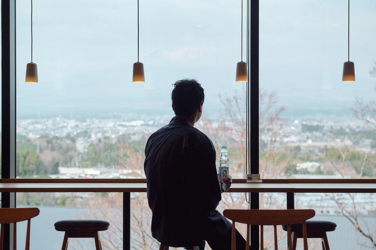 外の景色を見ながらラムネを飲む男性