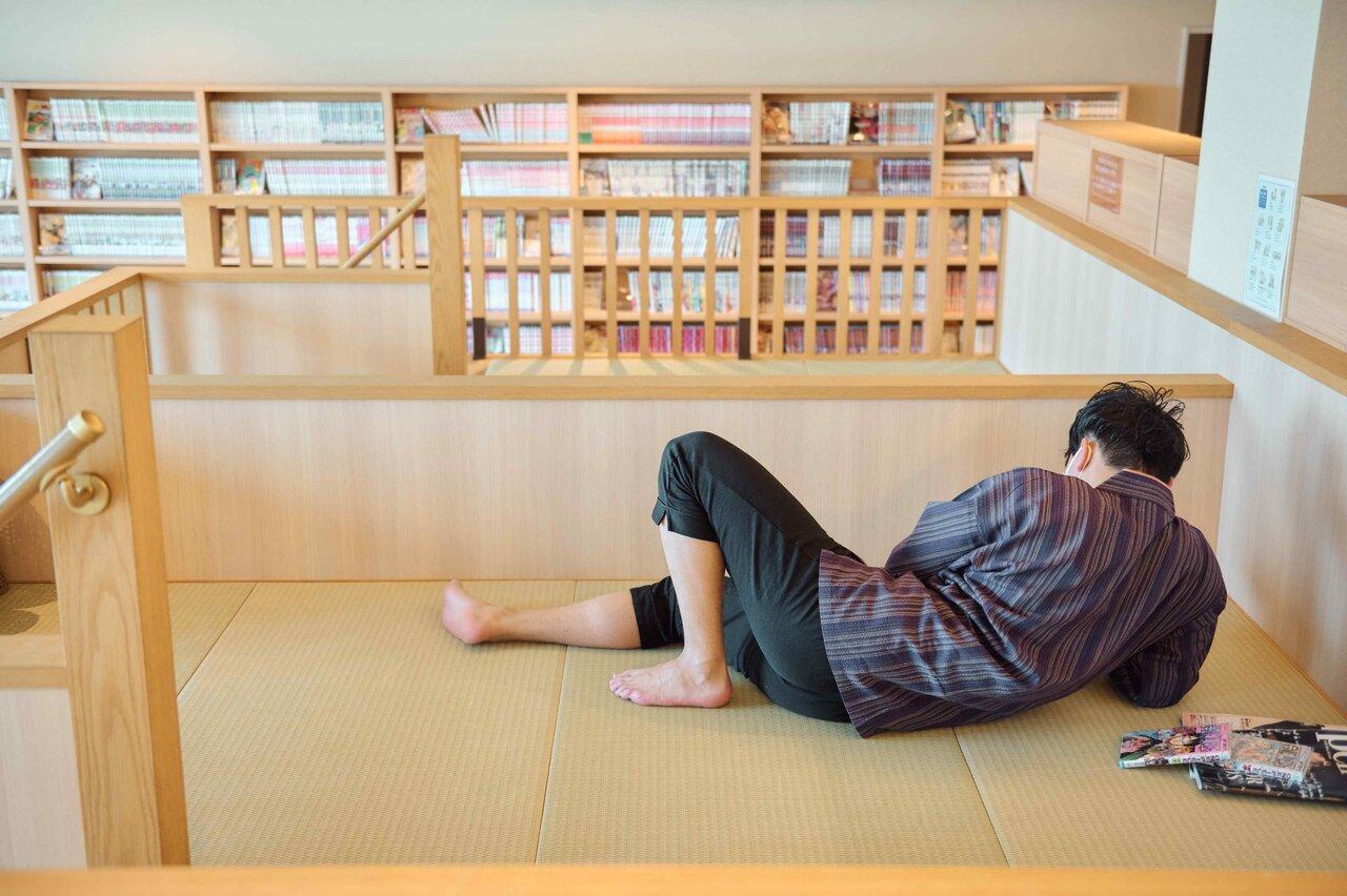 横に寝転んで漫画を読む男性