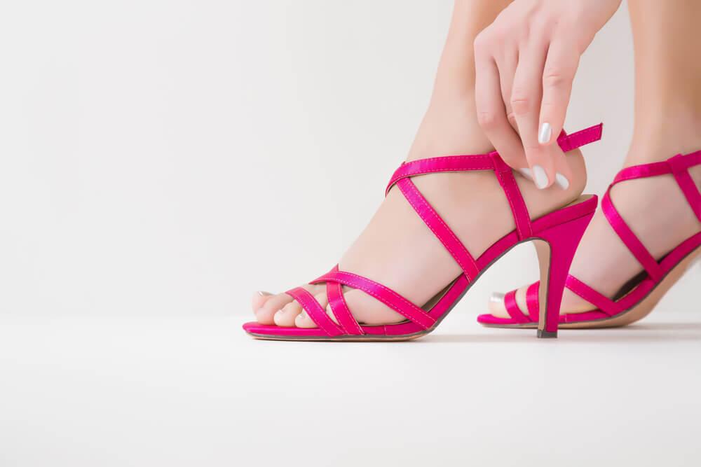 ピンクのアンクルストラップサンダルを履く女性