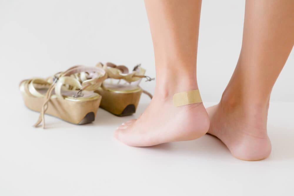 靴擦れに絆創膏を張っている若い女性の脚