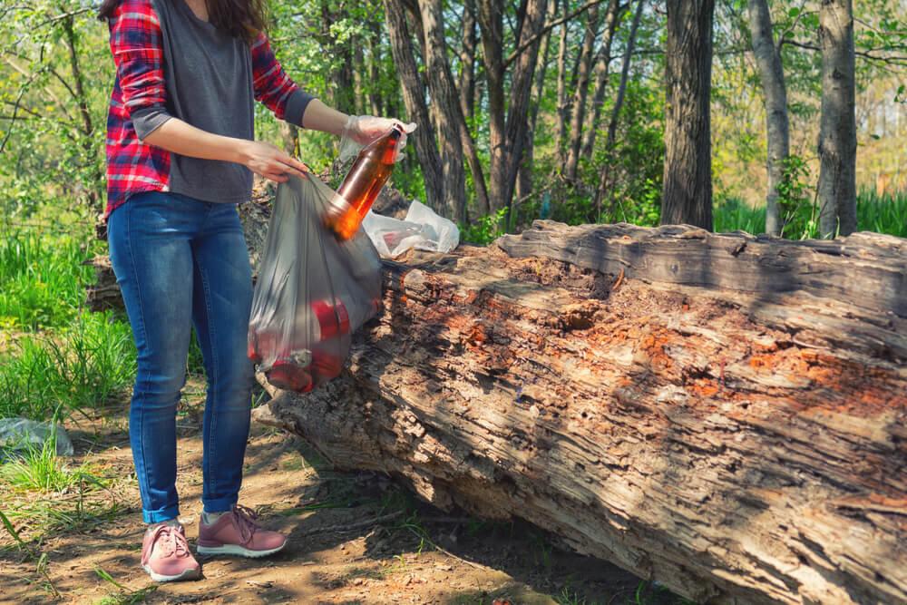 ゴミを拾ってビニール袋に入れる女性