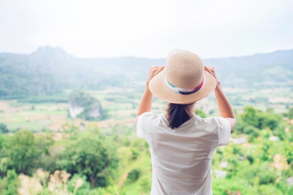 麦わら帽子をかぶって絶景を楽しんでいる女性