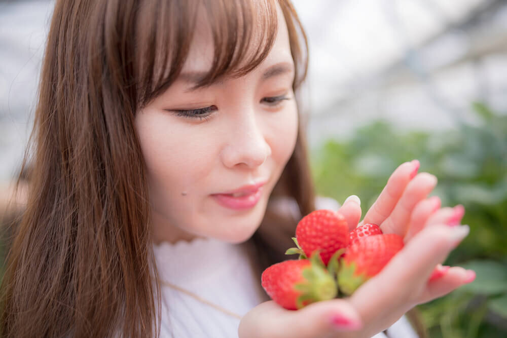 手の平にたくさんの苺をのせている若い女性