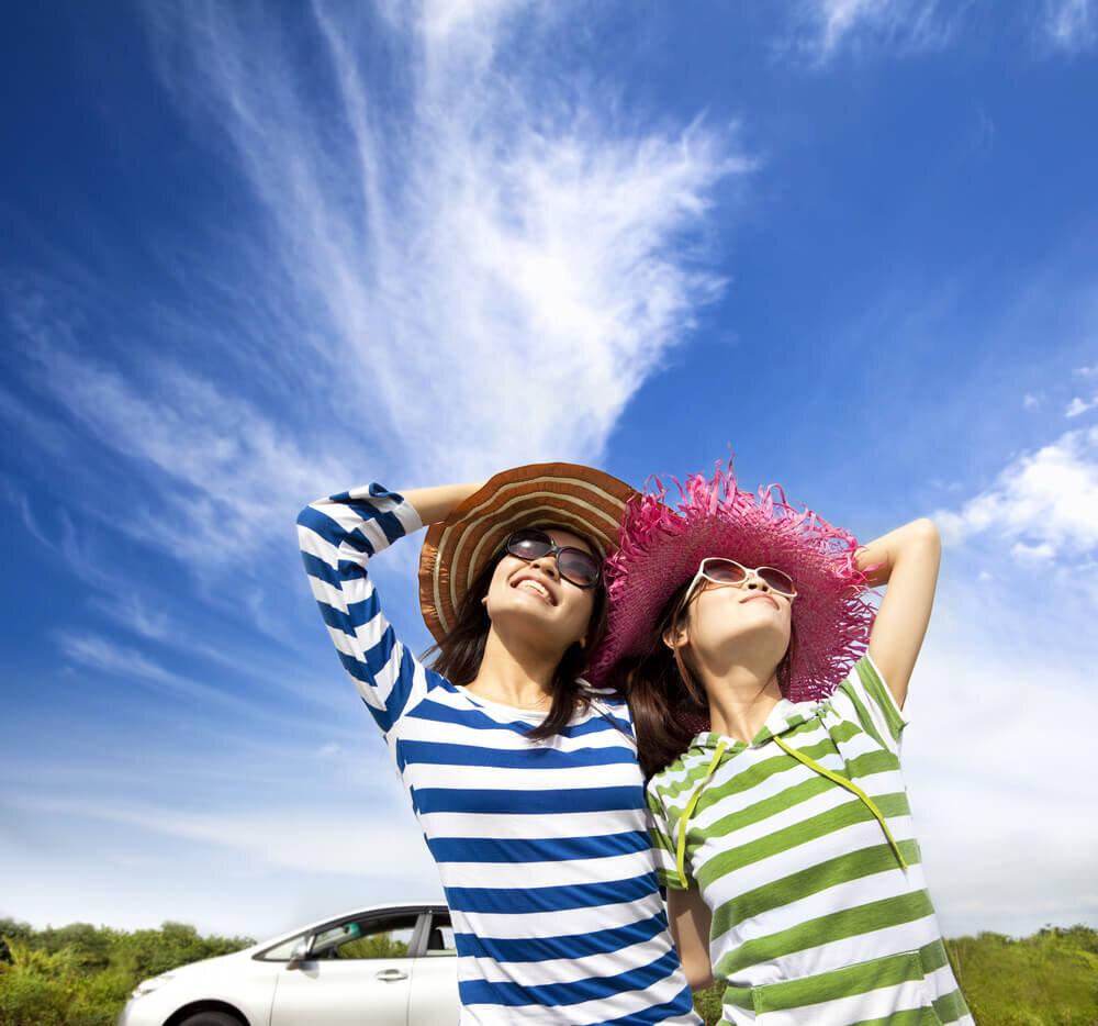 車の前で空を見上げる女性達