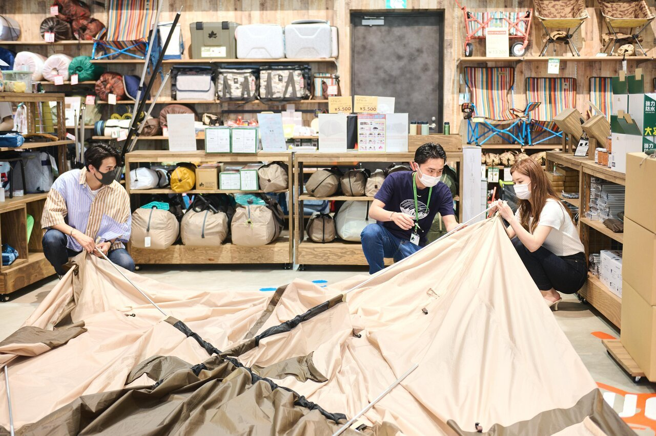 スタッフと一緒にテントの組み立て体験をするふたり