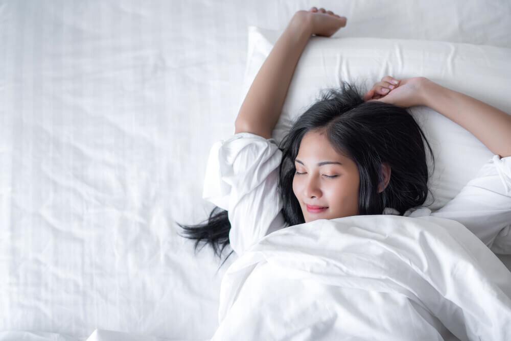 ベッドで快眠している若い女性