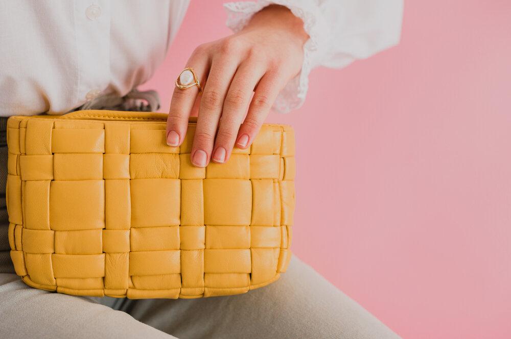 ベーシックカラーコーデに派手色のバッグをプラスした女性