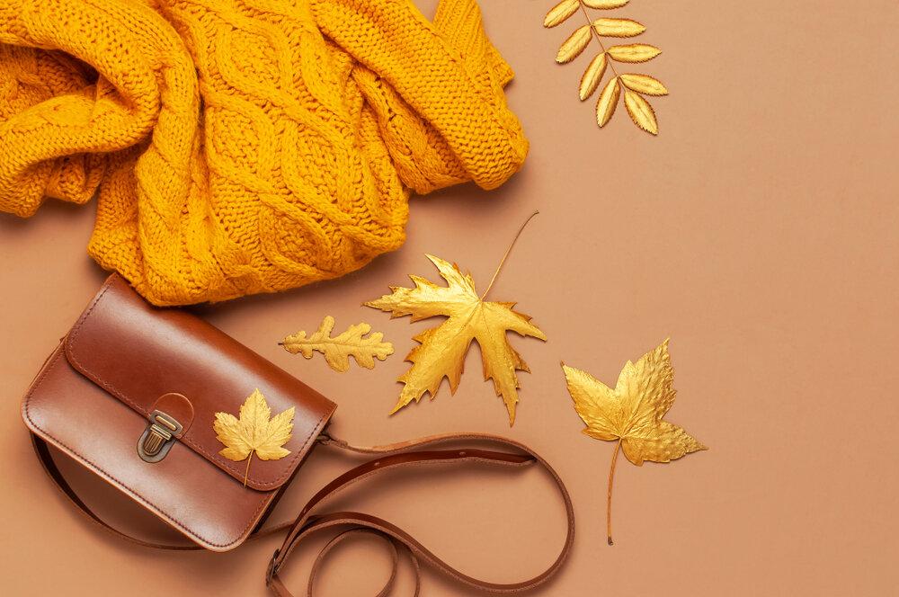 マスタードイエローのセーターとブラウンのバッグ