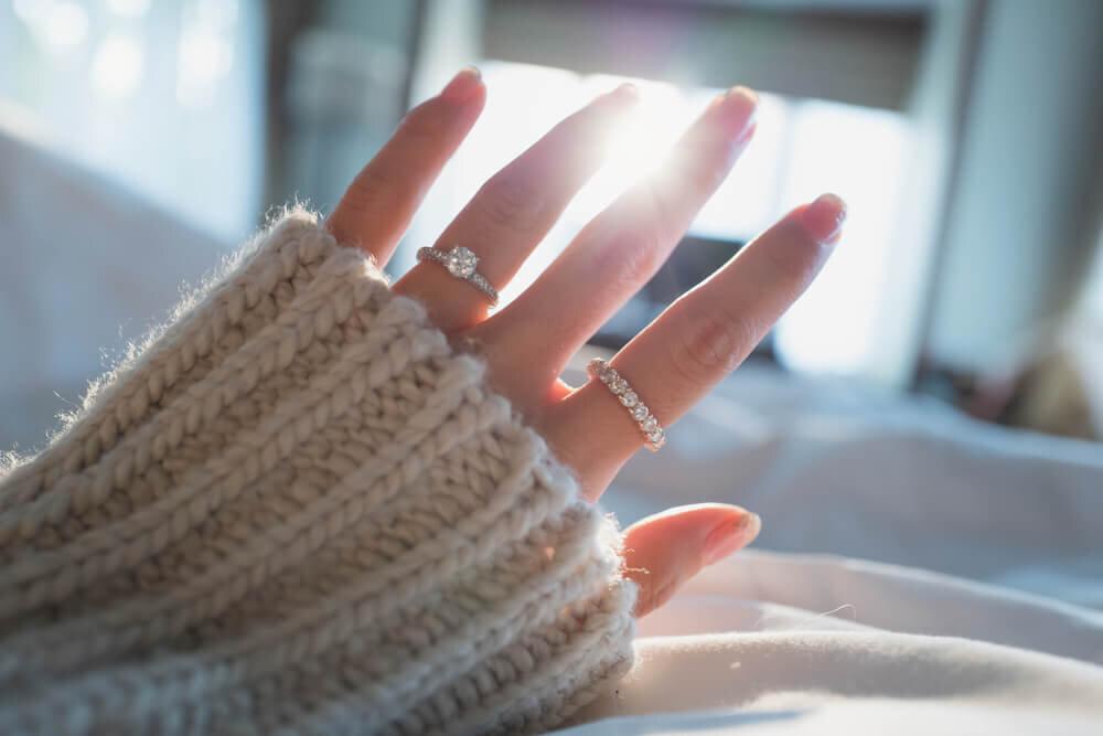 朝の光に向かって指輪を付けた手を広げる女性