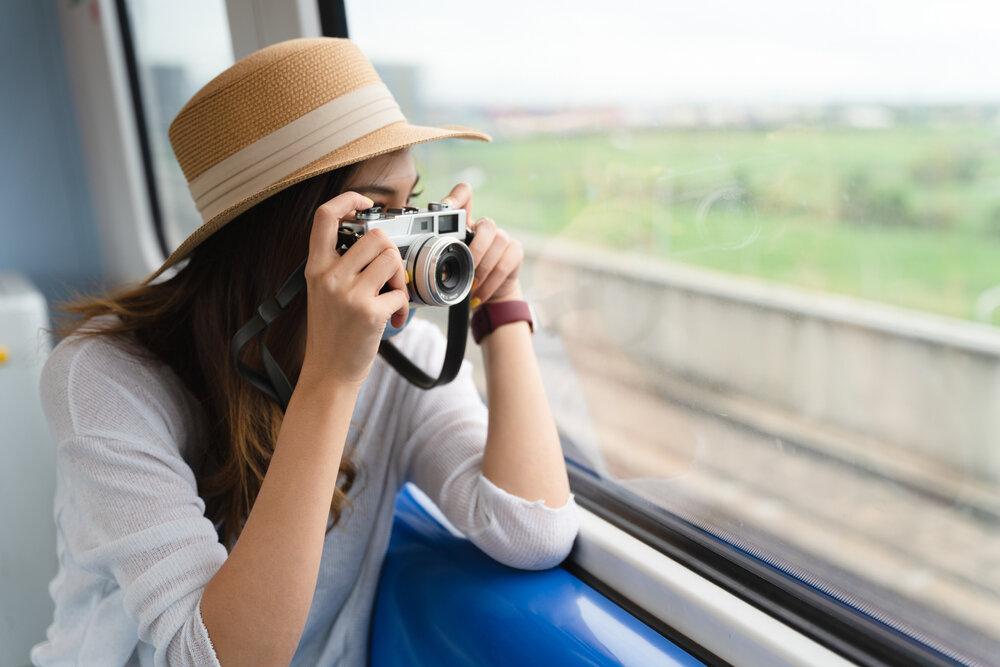 電車の窓から景色の写真を撮る女性