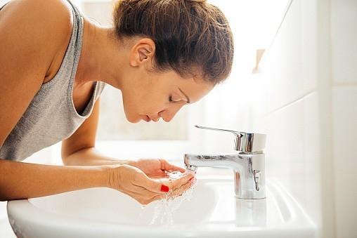若い女性が明るく朝の衛生のバスルーム