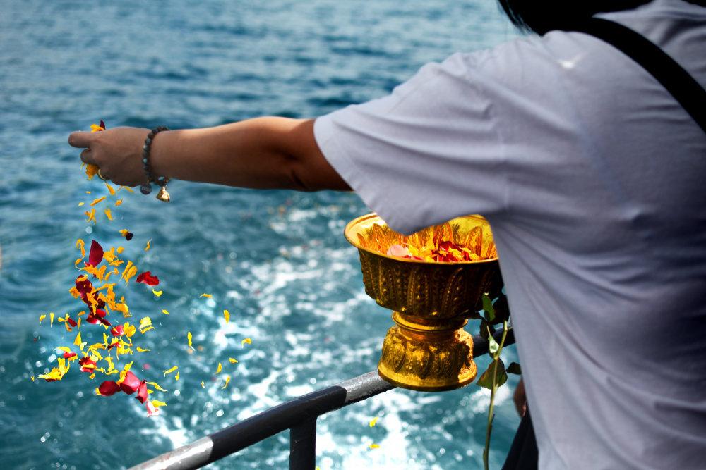 海で花びらをばらまく男性