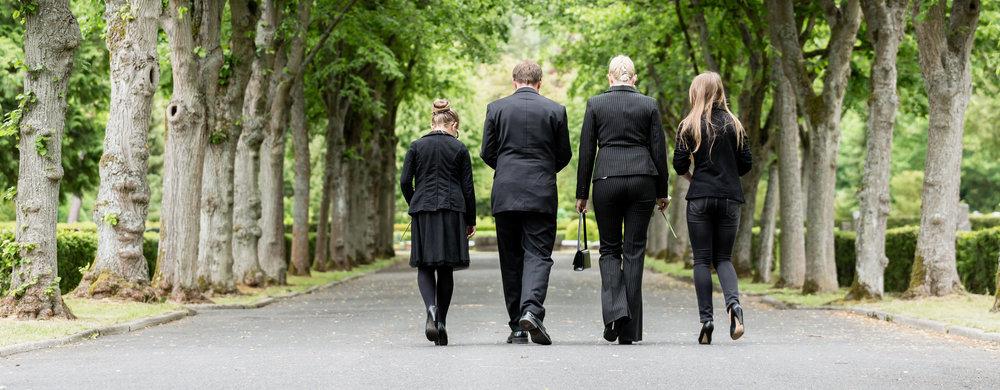 墓地の小道を歩く家族