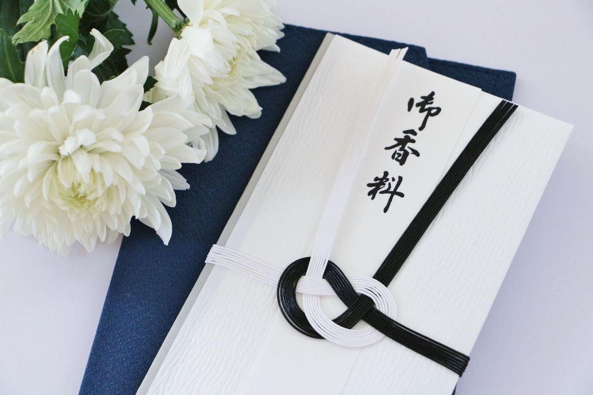 机に置かれた香典袋と白い花
