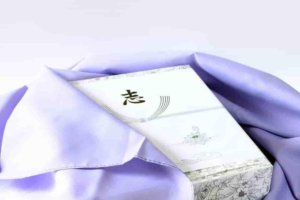 机に置かれた香典袋と白い菊の花