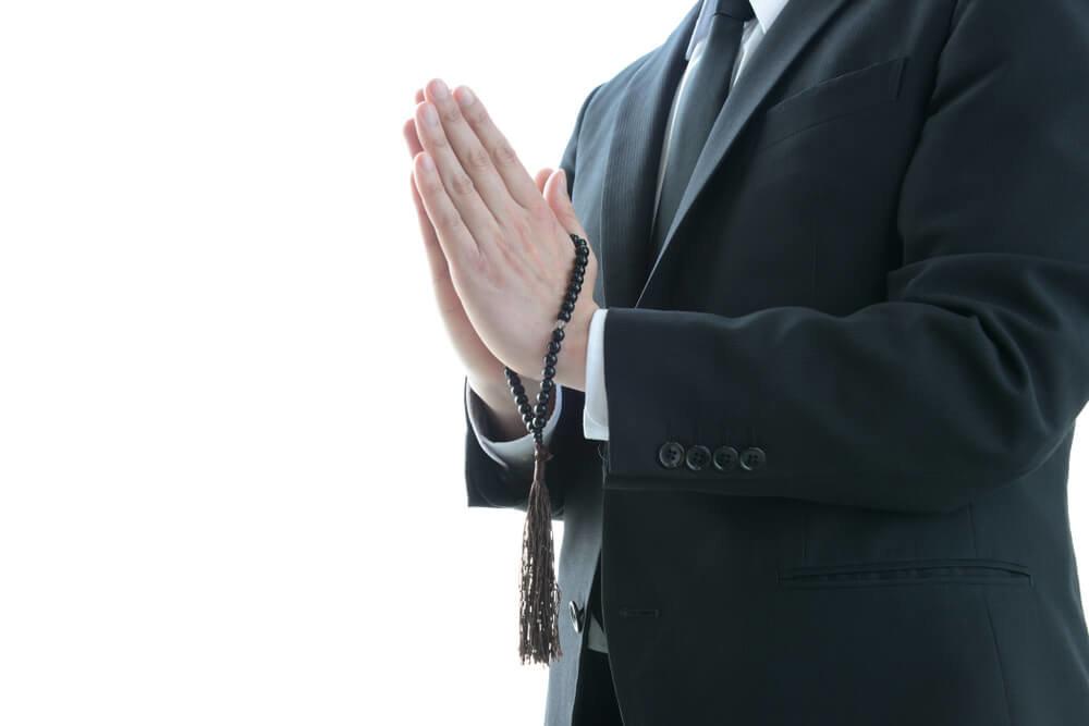 喪服で手を合わせる男性