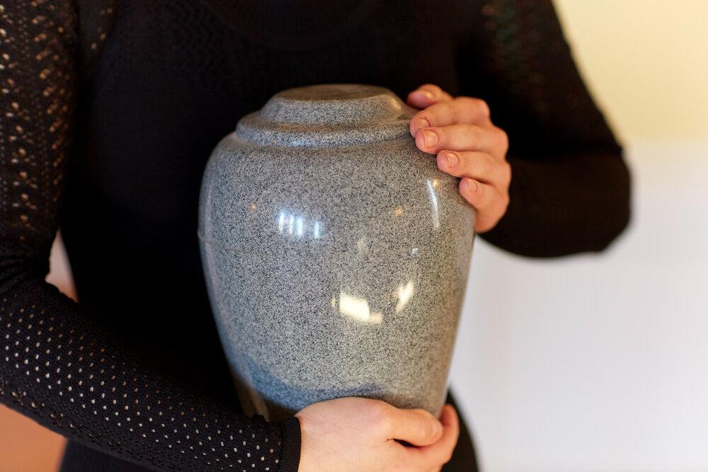 骨壺を抱える女性