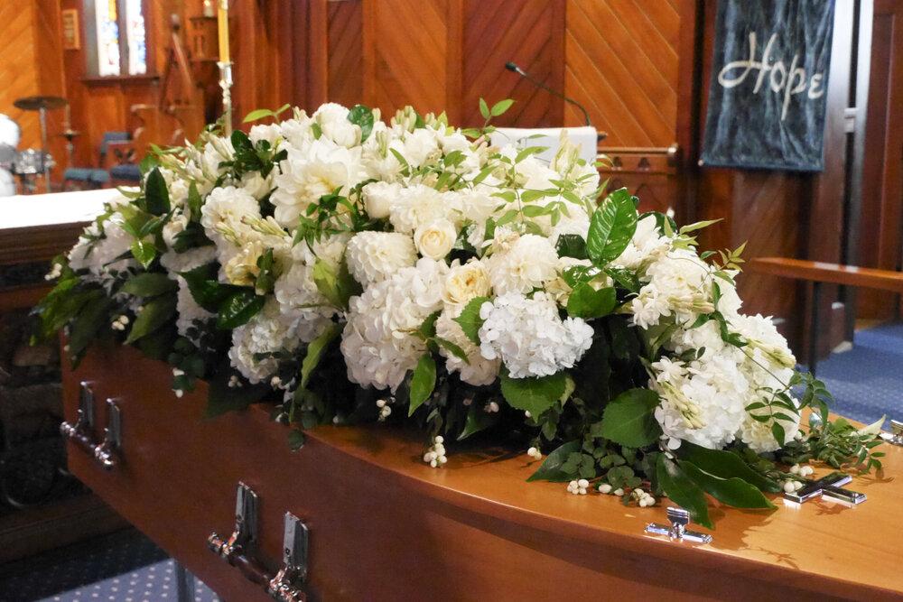 花がたくさんのせられた棺桶