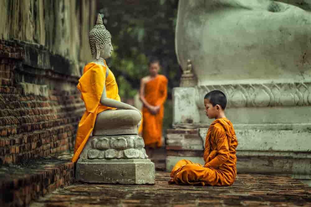 仏像に向かって瞑想する子ども