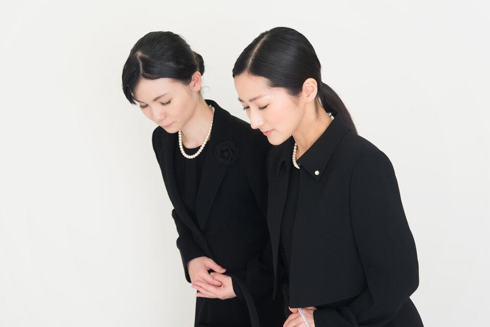 喪服を着てお辞儀をする2人の女性