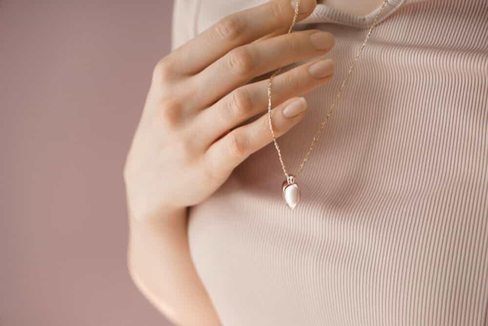 ネックレスに手を添える女性