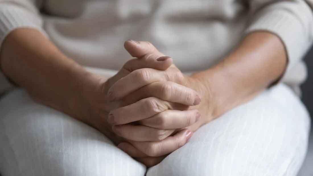 膝の上で手を組む女性