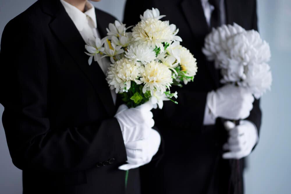 喪服を着て花を持つ人々