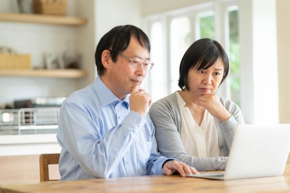 パソコンを見つめる夫婦