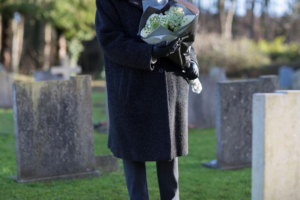 お墓の前で花を持ちたたずむコートを着た人物