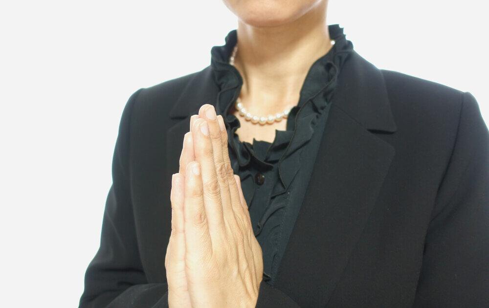 喪服で合掌をする女性