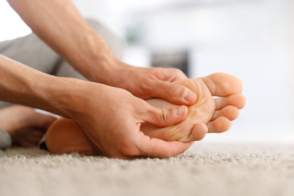 足をマッサージする両手