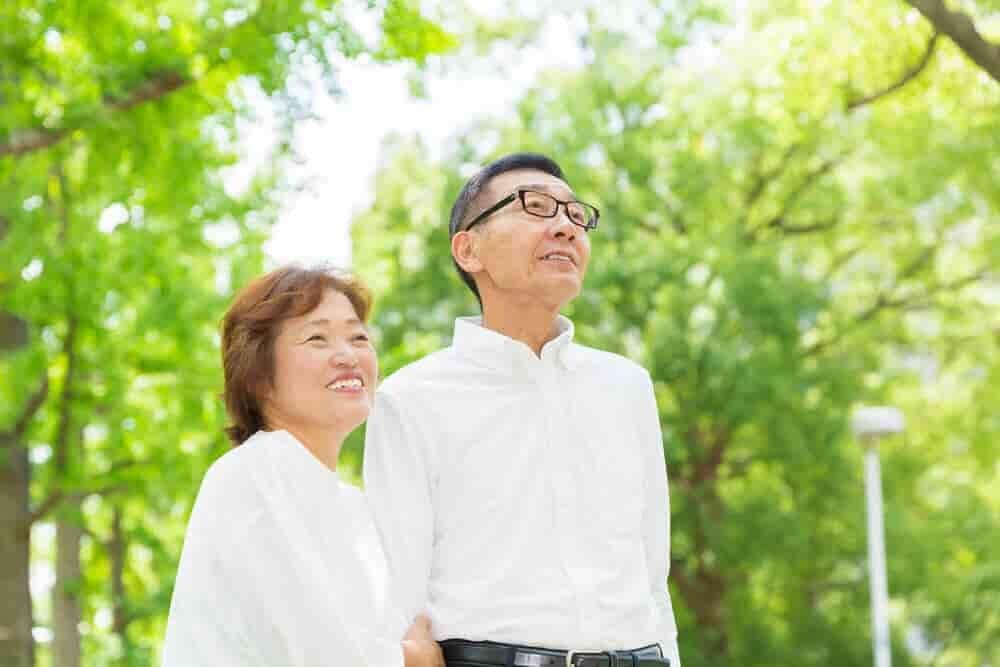 森林の中で微笑む初老の夫婦