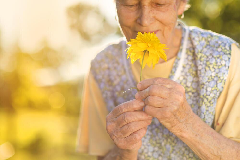 黄色い花を持つ老女